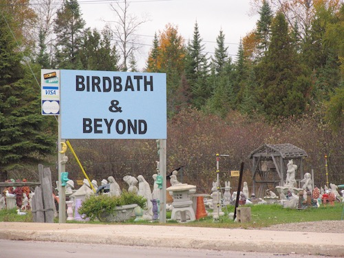 Birdbath and Beyond sign outside of yard decoration shop in rural area