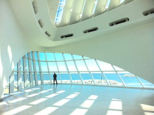 In a large sunlit hall with curving white walls, a silhouetted figure faces away toward blue water and sky